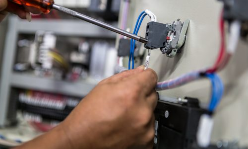 Electricians hands repair switches in electric control